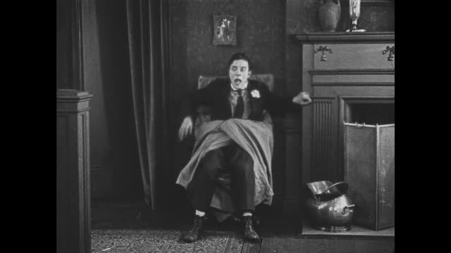 vídeos de stock e filmes b-roll de 1921 man (buster keaton) is terrified by hugging chair and climbs up banister to escape - mansão imponente