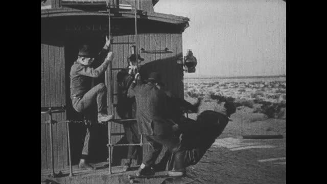 vidéos et rushes de 1918 man (fatty arbuckle) is thrown off of a train into the wild west - donner un coup de pied