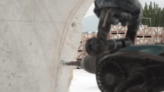 l'uomo utilizza uno strumento di perforazione su un blocco di marmo - marmo roccia video stock e b–roll