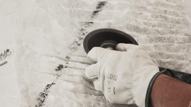 l'uomo usa lo strumento emery sul blocco di marmo - marmo roccia video stock e b–roll