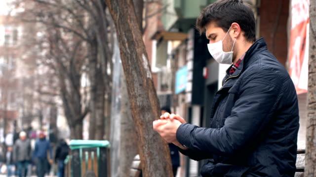 男子在公共區域使用帶面罩的手消毒器。冠狀病毒症狀。 - 行人路 個影片檔及 b 捲影像