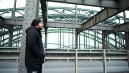 Man is walking across the bridge