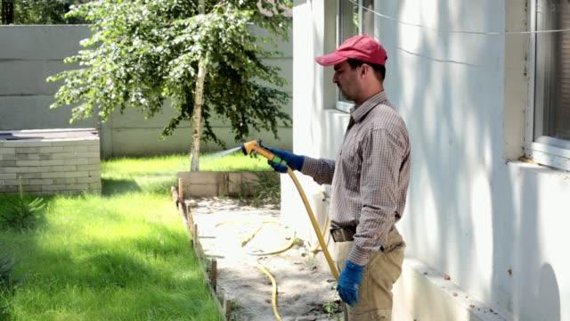 vídeos de stock e filmes b-roll de a man is watering a lawn near the house. - jardinagem