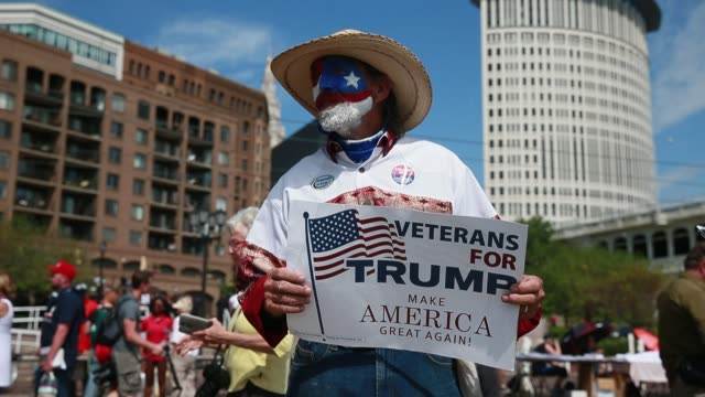 a man is wears the colors of the usa as face paint as donald trump supporters hold an america first rally at settlers square during the first day of... - 1日目点の映像素材/bロール