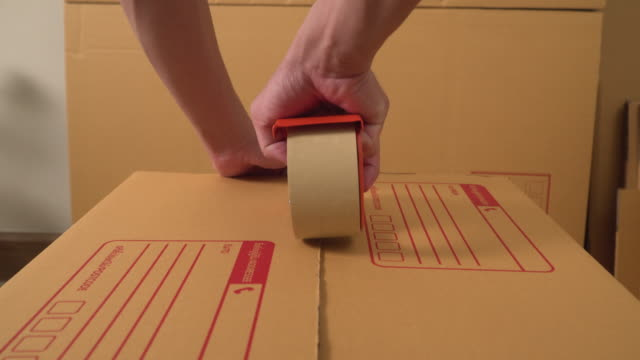 (dolly)a man is wrapping up the packaging box for delivery. - wrapping stock videos & royalty-free footage