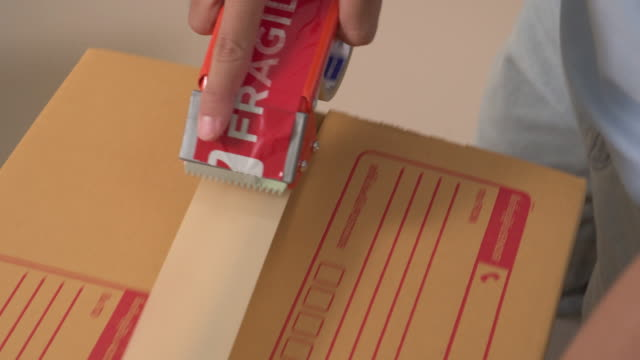 a man is wrapping up the packaging box for delivery. - stock trader stock videos & royalty-free footage
