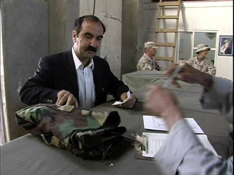 man issuing military uniform to mature recruit / afghanistan - operazione enduring freedom video stock e b–roll