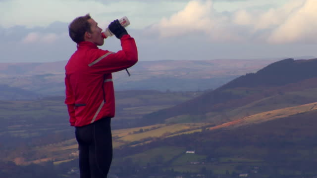 MS, Man jogger drinking water on hilltop and running away, Wales, United Kingdom