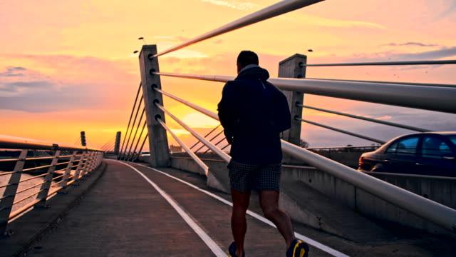 SLO MO homem Jogging ao longo de uma ponte em Anoitecer