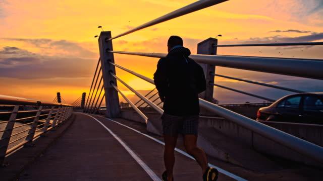 SLO MO homem Jogging através de uma ponte