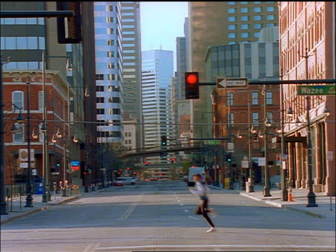 vídeos de stock e filmes b-roll de man jogging across city street / traffic in background / denver, colorado - denver