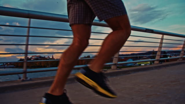 TS Man Jogging Across The Bridge At Dusk