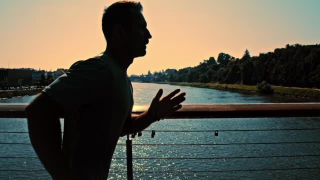 SLO, MO, Mann Joggen auf der Brücke in der Abenddämmerung