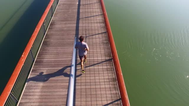 AERIAL Man jogging across the bridge
