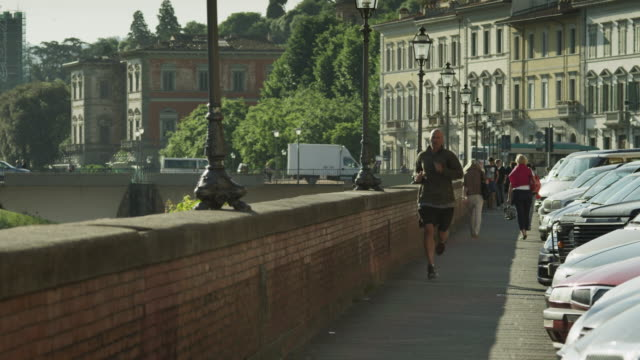 ws man jogging along ledge by river arno / florence,tuscany - newoutdoors stock videos & royalty-free footage