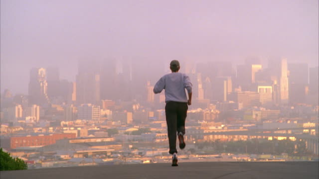 WS SLO MO Man jogging, cityscape in background / San Francisco, California, USA