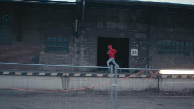 vídeos de stock e filmes b-roll de homem jogging em abandonado área de linha férrea - treinar