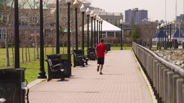 vidéos et rushes de man jogging in liberty state park - parc naturel