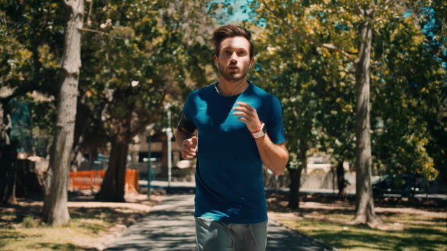 man jogging in park - jogging stock videos & royalty-free footage
