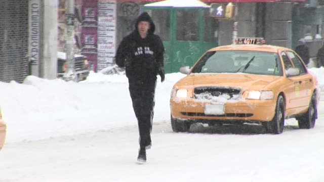 WS PAN Man jogging in snowy street as taxis drive by/ New York City