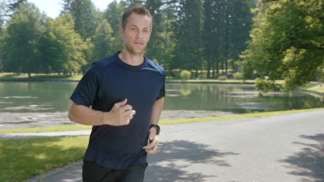 SLO MO-TS Mann Joggen im park an einem See