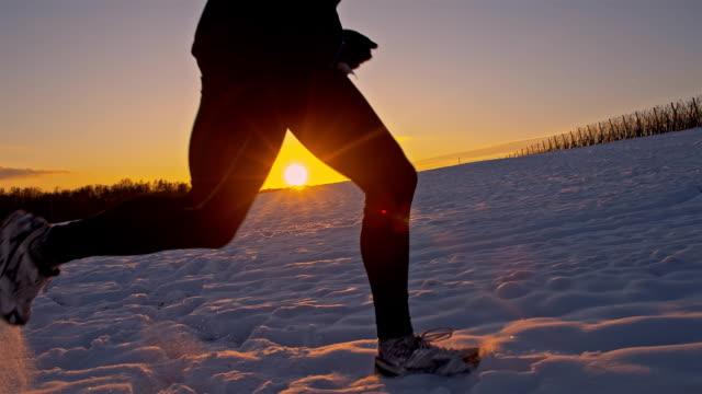 stockvideo's en b-roll-footage met slo mo man jogging in the snow - uithoudingsvermogen