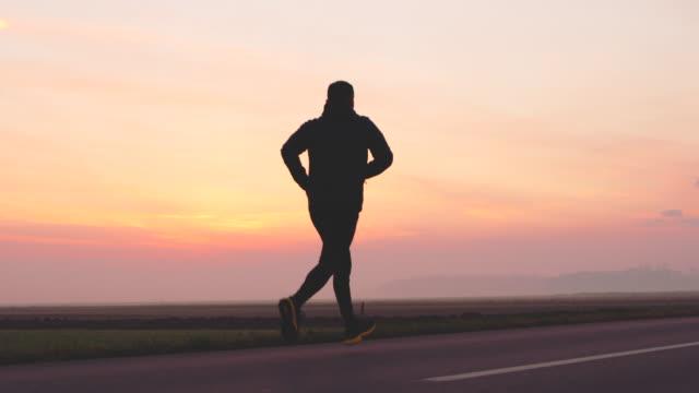 WS-Man Joggen auf einer Landstraße bei Sonnenuntergang