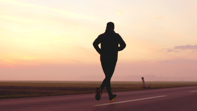 vídeos de stock e filmes b-roll de slo mo man jogging on a country road at sunset - full length