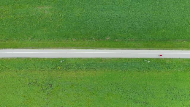 vidéos et rushes de homme faisant du jogging sur un chemin à travers des prairies verdoyantes - voie piétonne