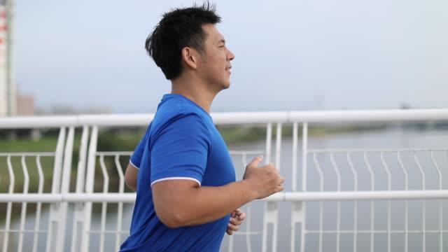 man jogging on city bridge - dieting stock videos & royalty-free footage