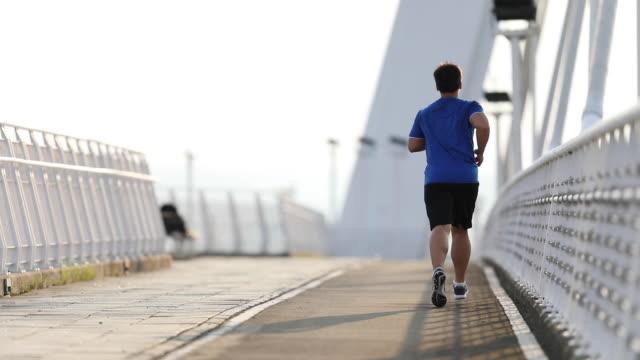 vídeos y material grabado en eventos de stock de hombre corriendo en el puente de la ciudad - overweight