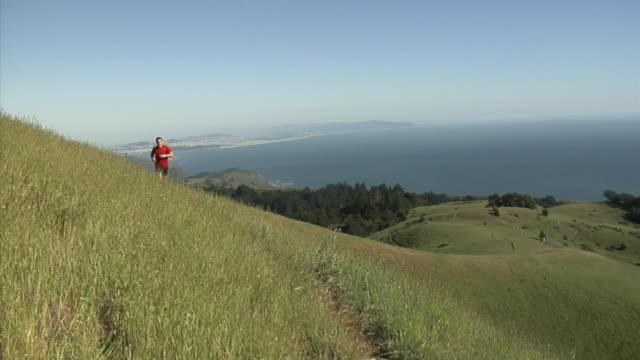 MS PAN Man jogging on hills overlooking sea, Mount Tamalpais, California, USA