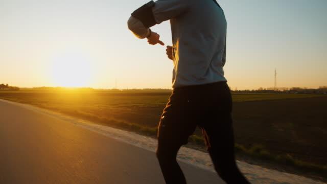 slo mo ms ts tu uomo che fa jogging su strada al tramonto - misurare il polso video stock e b–roll