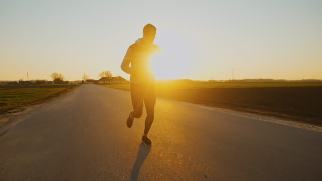 slo mo ws ts man jogging on road at sunset - cross country running stock videos & royalty-free footage