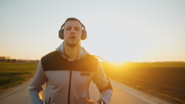 slo mo ms ts td man jogging on road at sunset - athlete stock videos & royalty-free footage