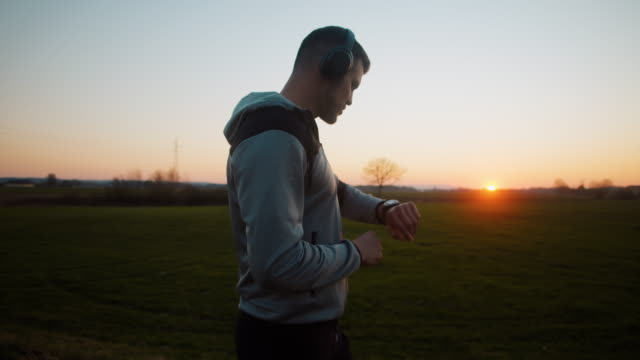 slo mo ms ts man jogging on road at sunset - headphones stock videos & royalty-free footage