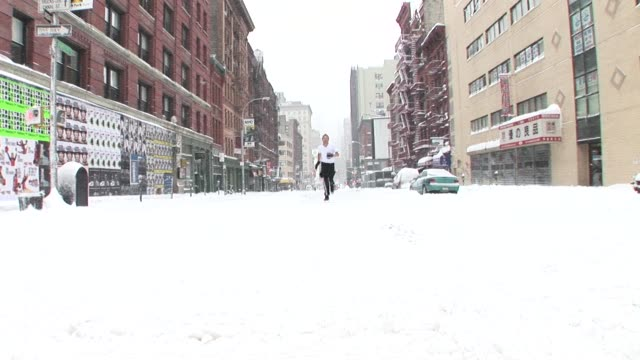 vídeos y material grabado en eventos de stock de ws man jogging on snowy street and sliding toward camera/ new york city - deslizar