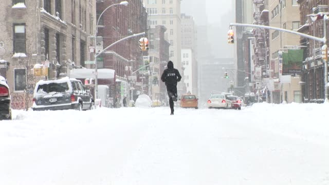 WS Man jogging on snowy street/ New York City