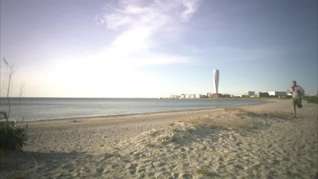 vídeos de stock e filmes b-roll de a man jogging on the beach malmo sweden. - região de oresund