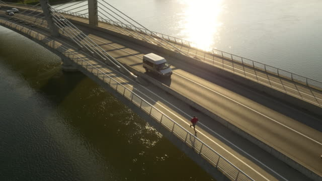 aerial man jogging on the bridge at sunset - next to stock videos and b-roll footage