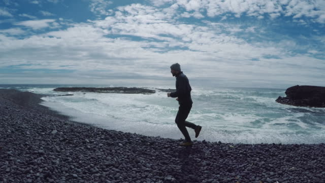 Man jogging on the rocky beach