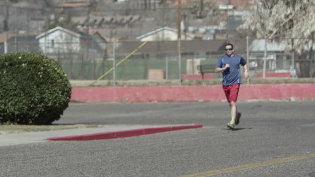 Man jogging on the street in suburban area with leg injury or cramp.