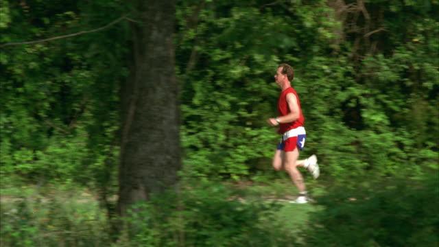 ws pan slo mo man jogging on trail through woods / johnson city, texas, usa - johnson city texas stock videos & royalty-free footage