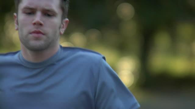 SLO MO CU SELECTIVE FOCUS Man jogging outdoors, Wilmington, North Carolina, USA