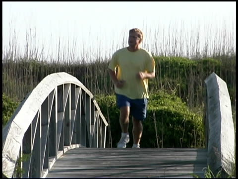 man jogging over bridge - one mid adult man only stock videos & royalty-free footage