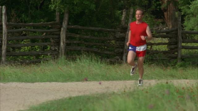 ws pan slo mo man jogging through field / johnson city, texas, usa - johnson city texas stock videos & royalty-free footage