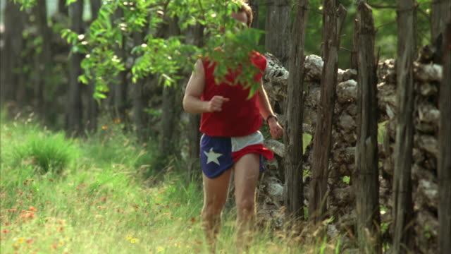 ms pan tu td slo mo man jogging through field / johnson city, texas, usa - johnson city texas stock videos & royalty-free footage