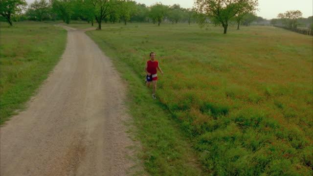 ws zi slo mo man jogging through field / johnson city, texas, usa - johnson city texas stock videos & royalty-free footage