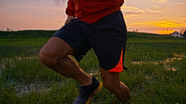vídeos de stock e filmes b-roll de slo mo homem jogging através de poças - vista lateral