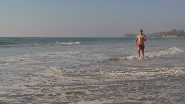 slo mo of man jogging through the water at the beach - badeshorts stock-videos und b-roll-filmmaterial